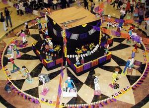 """En el atrio de la plaza comercial se ha montado el altar principal. Veladoras y cempasúchil delimitan la ofrenda de los """"muertos para los muertos""""."""
