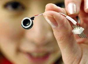 Una modelo muestra un dispositivo microscópico desarrollado por CANON Corp., para el uso de teléfonos móviles durante una exhibición de micromáquinas en Tokyo.
