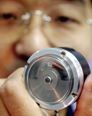 Un empleado de EPSON muestra un pequeño dispositivo compacto que produce  energía con su propio movimiento oscilatorio durante una exhibición en Tokyo.