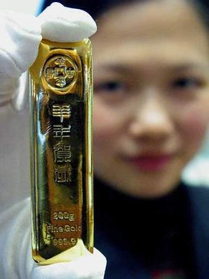 Una mujer oriental muestra una barra de oro de 200 gramos llamada Sman Yellow Creaker en una tienda en la ciudad de Nanjing, China. Por primera vez desde los años 50´s, las barras de oro podrán ser comercializadas privadamente en este continente.