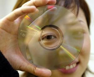 Un empleado de la Compañía japonesa DT Japan Inc. presume el que dice ser el primer disco compacto transparente en el mundo. El disco traslúcido usa plata en lugar de aluminio utilizado en los actuales y su grosor es de tan sólo 28  micrones que permiten al disco ser traslúcido pero con un efecto de reflección similar al del aluminio.