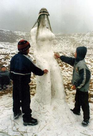 Niños nepaleses que residen en la India hacen una mujer de nieve cerca de la frontera India-Nepal.