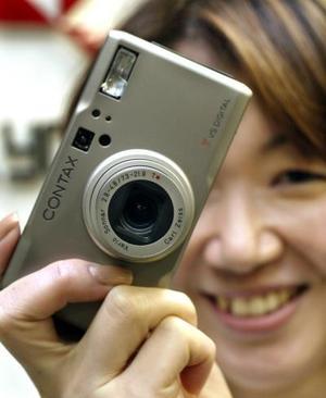 Una empleada muestra la nueva cámara digital Conax TVS en Tokio. La cámara mide 112 x 60 mm. Salió a la venta en febrero en Japón con un costo de $1000 USD.