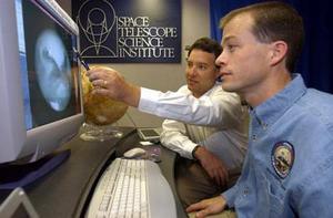 Los astrónomos estadounidenses Jim Bell (izq)  de la Universidad Cornell y Mike Wolff del Instituto de de Ciencia Espacial revisan las fotografías del planeta Marte tomadas por el 'Hubble Space Telescope'
