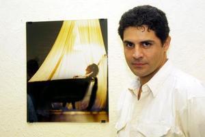 Arturo Valenzuela juntoa  una de las imágenes de su exposición Espejos Íntimos