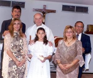 La niña Irma Román García en su Primera Comunión en la capilla de San Belarmino acompañada de sus padres y padrinos.