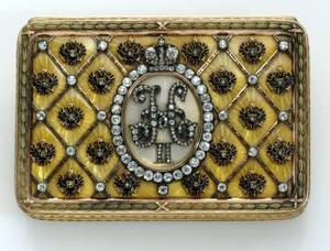 Encargados por primera vez por el zar ruso Alejandro III en 1885 como regalo de Pascua para su esposa, Maria Feodorovna, la tradición de los huevos elaborados por la firma Fabergé fue continuada por su hijo y sucesor, Nicolás II, convirtiéndose en una tradición familiar que se prolongó 30 años. <u> Imagen:La caja de la coronación </u>