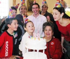 <u> 25 de enero </u> <p>  Señora Estela García de Reed al momento de apagar las velas de su pastel de cumpleaños rodeada de familiares.