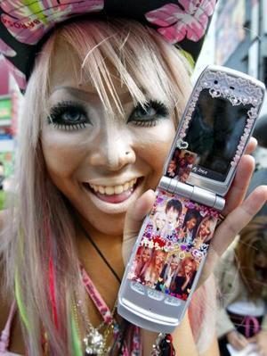 Una Shibuya Girl muestra su teléfono móvil cubierto con calcomanías en una calle de Tokio. La gente joven de la capital japonesa ha adoptado un 'look'  hippie.