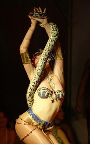 Un miembro del show artístico 'Eros' baila con una serpiente enrollada en su cuerpo durante la exhibición Internacional de este espectáculo en Moscú.