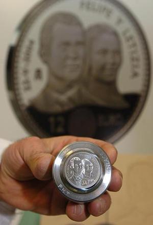 Un empleado español muestra la nueva moneda con los rostros grabados de la nueva pareja real