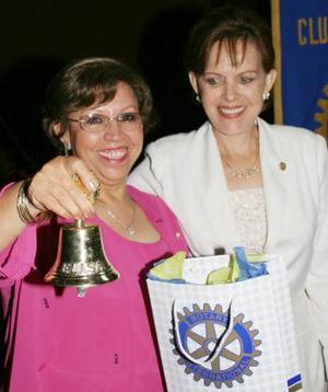 La señora Jose ávila de Ruiz recibe de manos de la esposa del gobernador rotario, Elisa Salazar de Morales, una campaña comio símbolo de la celebración de los 100 años de Rotary.