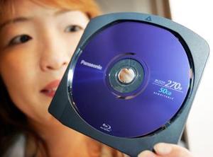 Una empleada de Matsushita Electric Industrial Co., muestra uno de los nuevos productos de Panasonic. <p> Es un disco DVD regrabable que almacena 50 Gigabytes, su costo es de 69 dólares y graba cuatro y media horas de alta calidad.