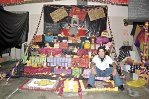 Luis Hernández, junto al altar que montaron los alumnos de sexto grado de la Escuela Carlos Pereyra, a los niños muertos en guerras.