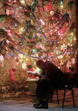 Un cubano lee el periódico cerca del árbolde Navidad que se encuentra cerca de la iglesia en La Habana.