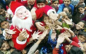 Un hindú vestido de Santa Claus reparte dulces a niños en una escuela en la ciudad de Chandigarh.