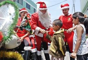 El escuadrón Fénix de la policía motorizada de Perú, disfrazada con el traje de Papa Noel, recorre las calles del barrio limeño de barrios altos.