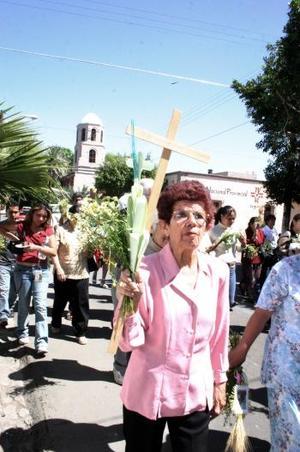Los católicos se persignaban y agachaban la cabeza cuando la figura de Jesucristo pasaba cerca de ellos, alzando sus ramos entre rezos.
