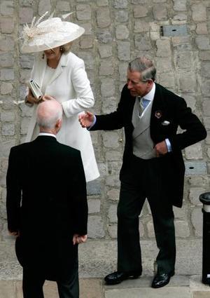 Sonriente, resplandeciente y ante la atenta mirada de británicos, fotógrafos y cámaras de televisión, Camilla lució un elegante gabán de seda en color perla sobre un vestido de gasa en igual tono, acompañado por una pamela a juego adornada con pequeñas plumas.  El príncipe, bronceado y al que se vio muy alegre, llevaba chaqué, una elección que distó mucho del uniforme militar que lució en su primera boda con Diana de Gales en 1981.