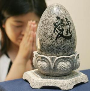 Una japonesa hace oración enfrente de un pequeño óvalo de granito donde descansan los restos de un difunto. Las tumbas de granito tienen un costo de 1611 dólares aproximadamente.