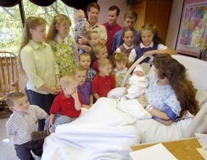 Michelle Dugger de Srpingdale Arkansas sostiene al Nuevo miembro de su familia, su hijo número 16 en el hostpital St Mary en Rogers Arkansas mientras que su esposo y sus demás hijos todos con nombre que inicia con la letra 'j' observan.