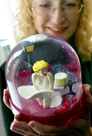 La directora del museo Eva Haupt muestra una bola de nieve que contiene una muñeca que representa a Marilyn Monroe en el museo de Isergbirg en Neugablonz (Alemania) .