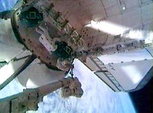 El astronauta Stephen Robinson, montado en el extremo de un brazo robótico de 50 metros de largo, retiró suavemente dos trozos de fieltro de relleno que sobresalían entre las losas de protección térmica del transbordador Discovery.