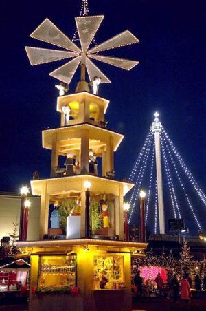 Vista de una pirámide de navidad frente a la Euro-Torre iluminada del parque temático Europa en Rust, Alemania.