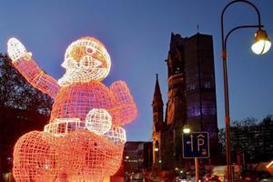Un enorme Santa Claus iluminado  fue captado al oeste de la ciudad de Berlín, Alemania. Detrás de la silueta está la iglesia Memorial Kaiser Wlhelm.