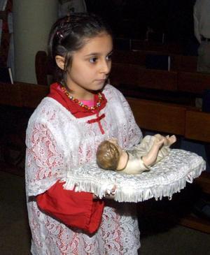 Una niña iraquí cristiana lleva una figura del niño Jesús durante la celebración de una oración en la Iglesia del barrio de Karrada, en el centro de Bagdad, Irak.