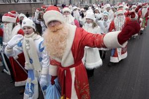 Varios hombres disfrazados de Santa  y mujeres vestidas de Doncella de la Nieve  participan en un desfile por las principales calles de Minsk Bielorrusia.
