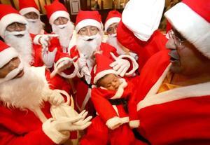 Trabajadores de un hotel de Yakarta, Indonesia se vistieron de Santa Claus, en la imagen posan con el bebé de uno de ellos durante la celebración navideña.