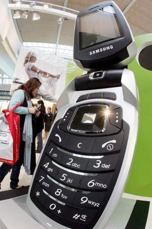 Una visitante frente a un teléfono móvil gigante en el pabellón de Samsung en la feria cebit de Hanover.