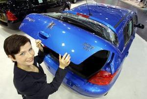 Una azafata posa junto a un Peugeot 307 HDI 90 FAP que alberga en su interior un nuevo motor diesel, en la Feria del Automóvil de Leipzig, Alemania.