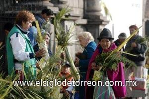 ECUADOR: Una mujer ofrece figuras hechas con hojas de palma, al inicio de la tradicional misa del Domingo de Ramos en la ciudad de Quito, Ecuador. (EFE)