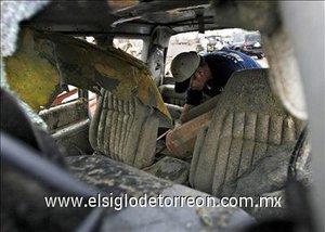 Un hombre recoge algunas cosas de la parte anterior de su camión que quedó desecho.