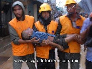 Un grupo de bomberos recupera el cuerpo sin vida de un niño tras los deslizamientos de tierra ocurridos al sur de Bangladesh.