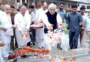 El ex ministro principal de Jammu y Cachemira decora unas tumbas en el Cementerio de los Mártires.