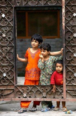 Tres niños observan a los manifestantes del grupo  separatista denominado Liga Musulman de Jammu y Cachemira mientras marchan hacia el Cementerio de los Mártires.