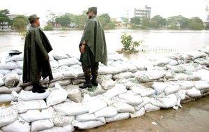 Miembros del Ejército mexicano vigilan desde un dique de contención que construyeron en la rivera del río Grijalva.
