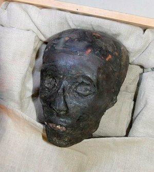 La momia de Tutankamón tiene la nariz aplastada, los dientes pronunciados y el rostro ennegrecido, que resalta sobre el sudario de lino con el que se ha envuelto su cuerpo enjuto para protegerlo.