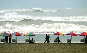 Varios turistas observan el mar en la playa más larga del mundo, Cox's Bazar en Bangladesh.