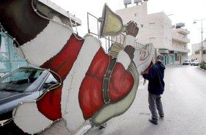 Un hombre transporta una figura gigante de papa Noel en la ciudad Cisjordana de Belén. Un año más se esperan en navidad gran cantidad de turistas ya que la ciudad de belén es conocida como lugar de nacimiento de Jesucristo.