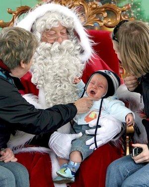 Santa Claus hacen sentir su presencia alrededor del mundo, aquí un bebe llora en sus brazos en Hyde Park  de Londres.