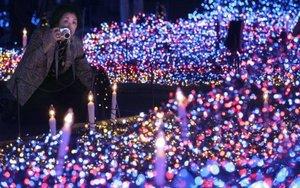 """Una mujer toma fotos de la iliminación navideña en Tokio, Japón, la cual fue titulada """"el Océano Azul, en donde se utilizaron más de 300 mil focos."""