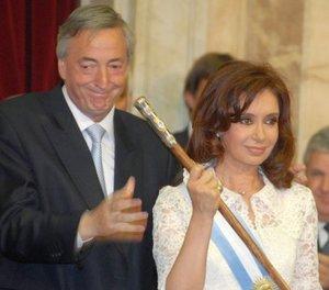 Néstor Kirchner, presidente saliente, entregó los atributos del mando, una banda con los colores argentinos celeste y blanco y un lujoso bastón fabricado por un orfebre local a su esposa, la ahora presidenta.