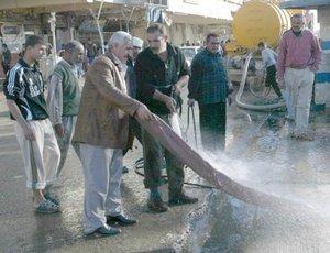 Iraquíes limpian el lugar en el que hizo explosión una bomba en un mercado en Amara, sur de Bagdad.