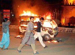 Personas pasan junto un automóvil incendiado durante una protesta protagonizada por los partidarios de Benazir Bhutto, que fue dos veces primera ministra de Pakistán y presidenta del partido de la oposición Partido del Pueblo de Pakistán (PPP).