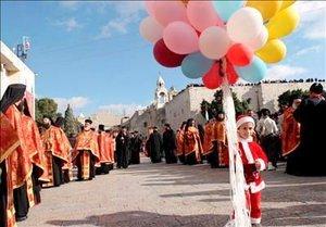 Un niño disfrazado de Santa Claus sostiene unos globos durante la procesión de la Iglesia griega ortodoxa cristiana celebrada en el exterior e interior de la iglesia de la Natividad con motivo de la Epifanía de los Reyes Magos.