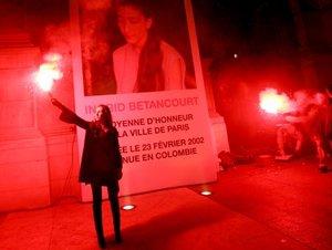 Simpatizantes de la ex candidata a la presidencia de Colombia Ingrid Betancourt encienden unas bengalas frente a un gran cartel con su retrato en París, Francia. Betancourt está en poder de las FARC desde hace casi seis años.